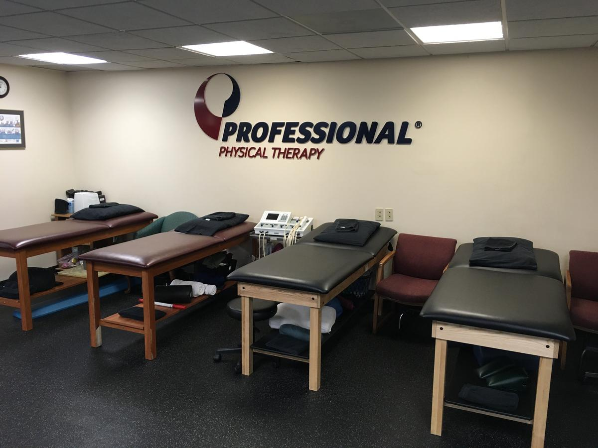 Interior with treatment tables and ProPt logo in our physical therapy clinic in Huntington, NY Long Island Suffolk County.