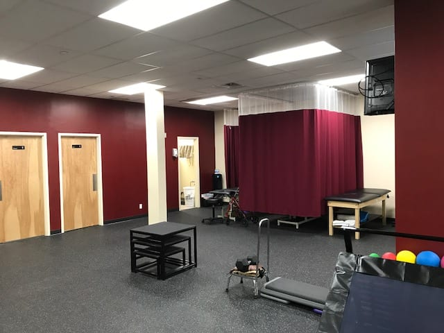 An image of our training room with maroon walls at our physical therapy clinic in Marine Park, New York.