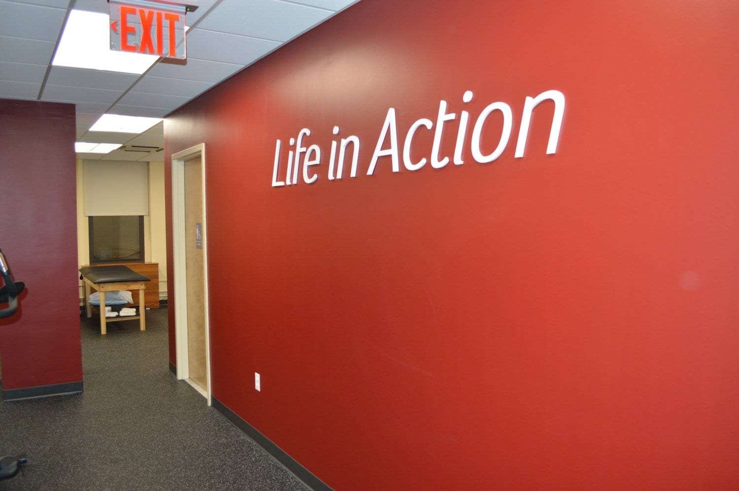 An image of a red wall at our physical therapy clinic in Brooklyn Heights, New York. There are words on the wall that say,