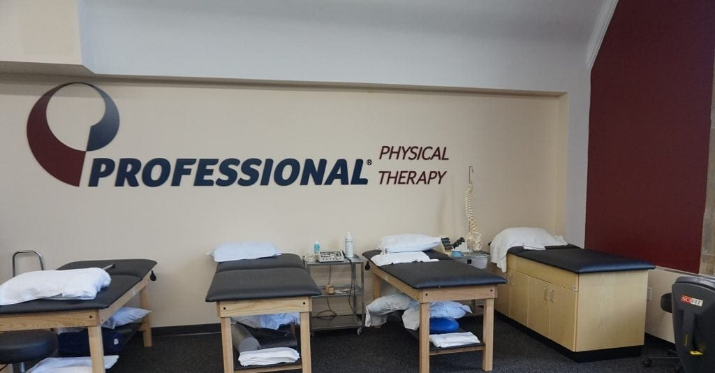 An image of stretch beds along a wall under the Professional Physical Therapy sign at our clinic in Hartsdale, New York.