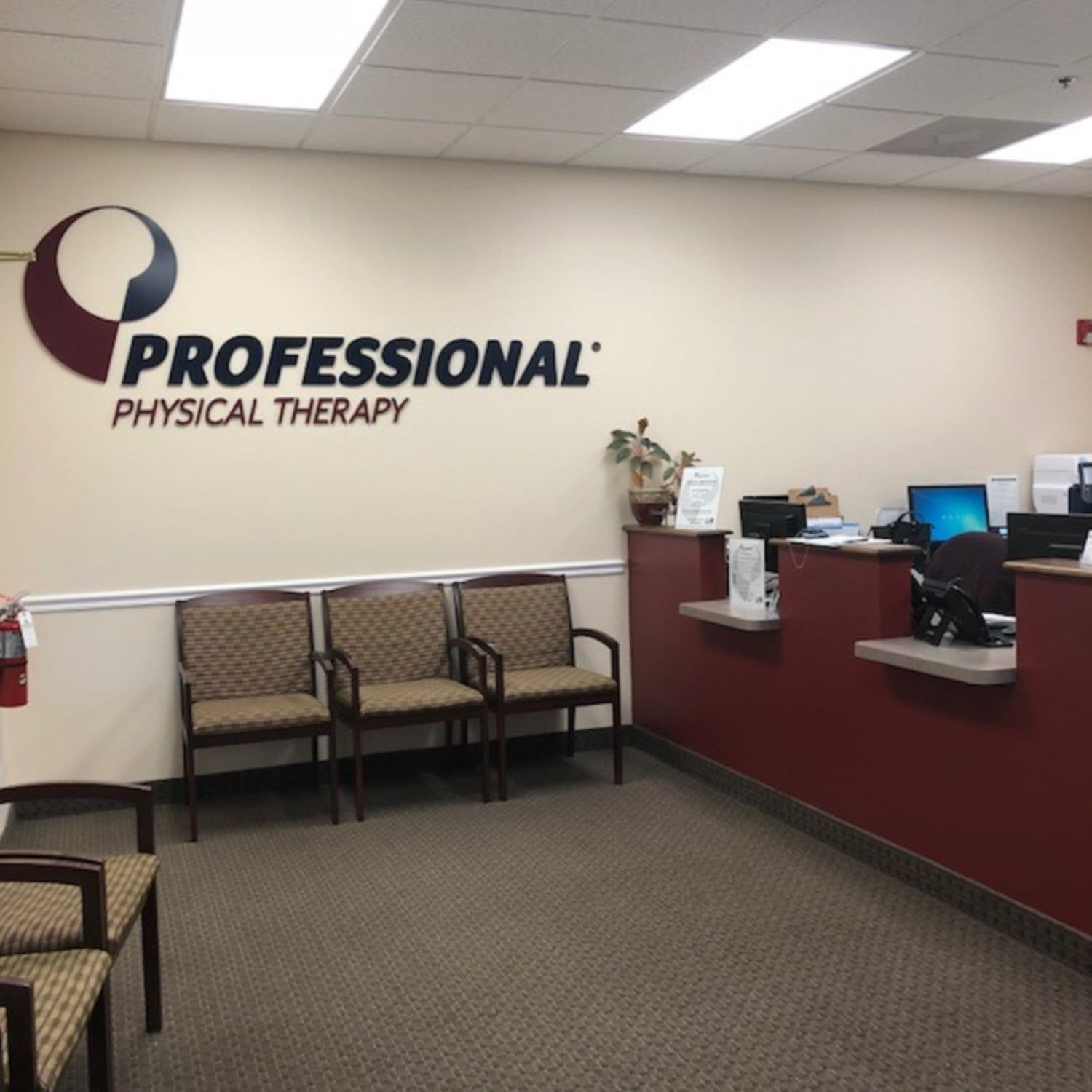 An image of the front desk and waiting area at our physical therapy clinic in Hazlet, New Jersey. The chairs are brown and the desk is red.