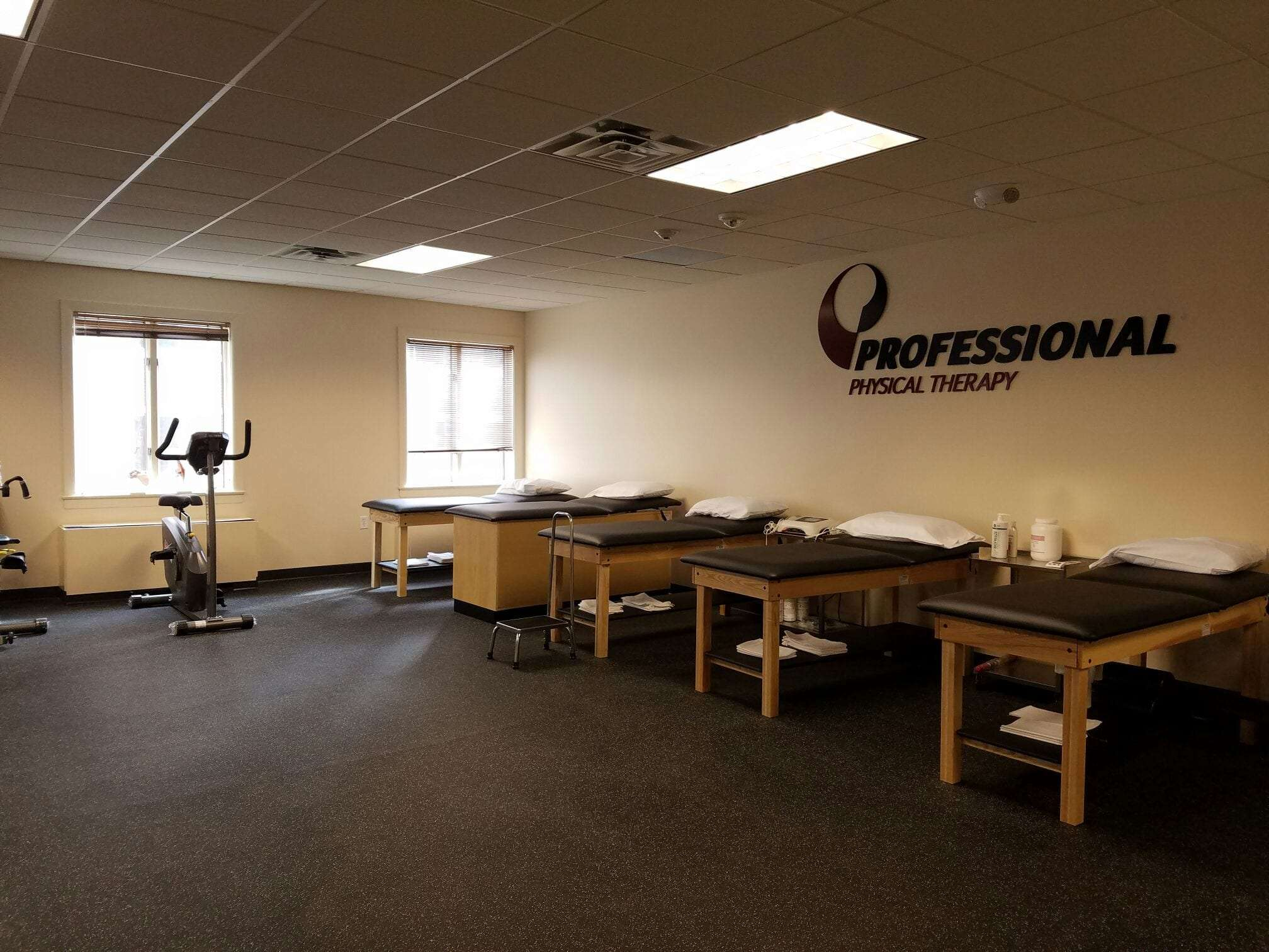 An image of five stretch beds and an elliptical in our training room at our physical therapy clinic in Hoboken, New Jersey.