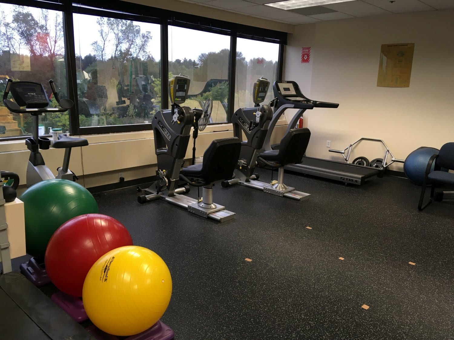 This is an image of two exercise machines and three workout balls used at our physical therapy clinic in Oradell, New Jersey. These balls are great for improving balance and flexibility.