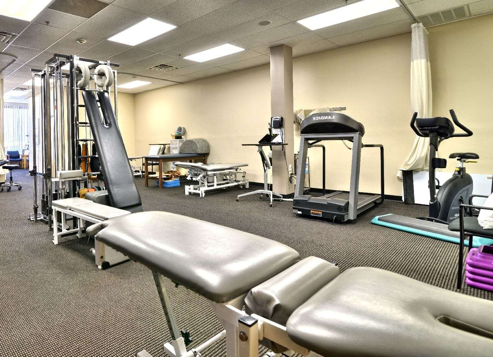 Here is a photo of a stretch bed and a treadmill at our physical therapy clinic in Haverhill, Massachusetts.