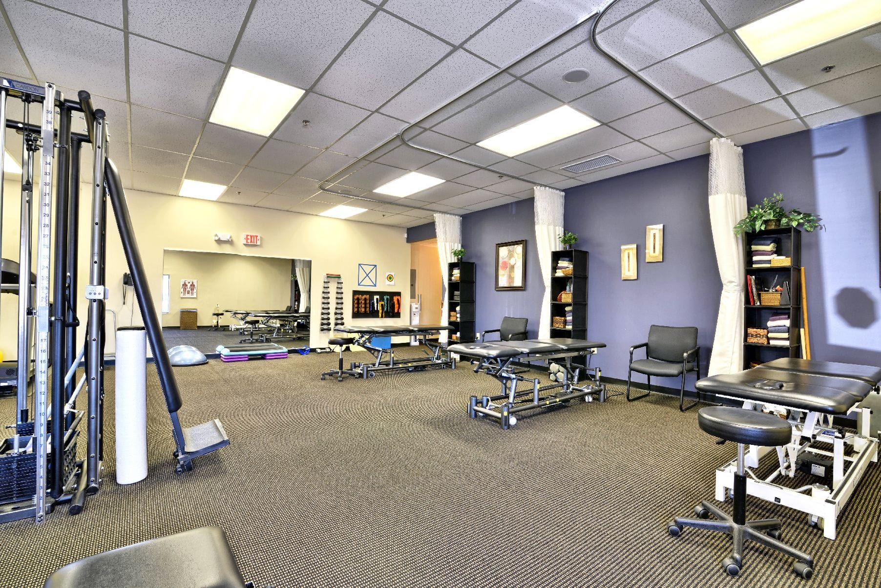 A photo of the interior of our physical therapy clinic in Middleton, Massachusetts. This photo shows stretch beds, weights, and a purple wall.