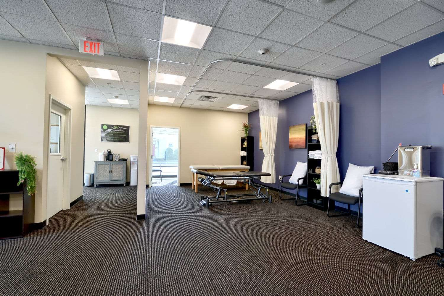 An image of the interior of our physical therapy clinic, showing a stretch bed and a fridge, at our facility in Waltham, Massachusetts.