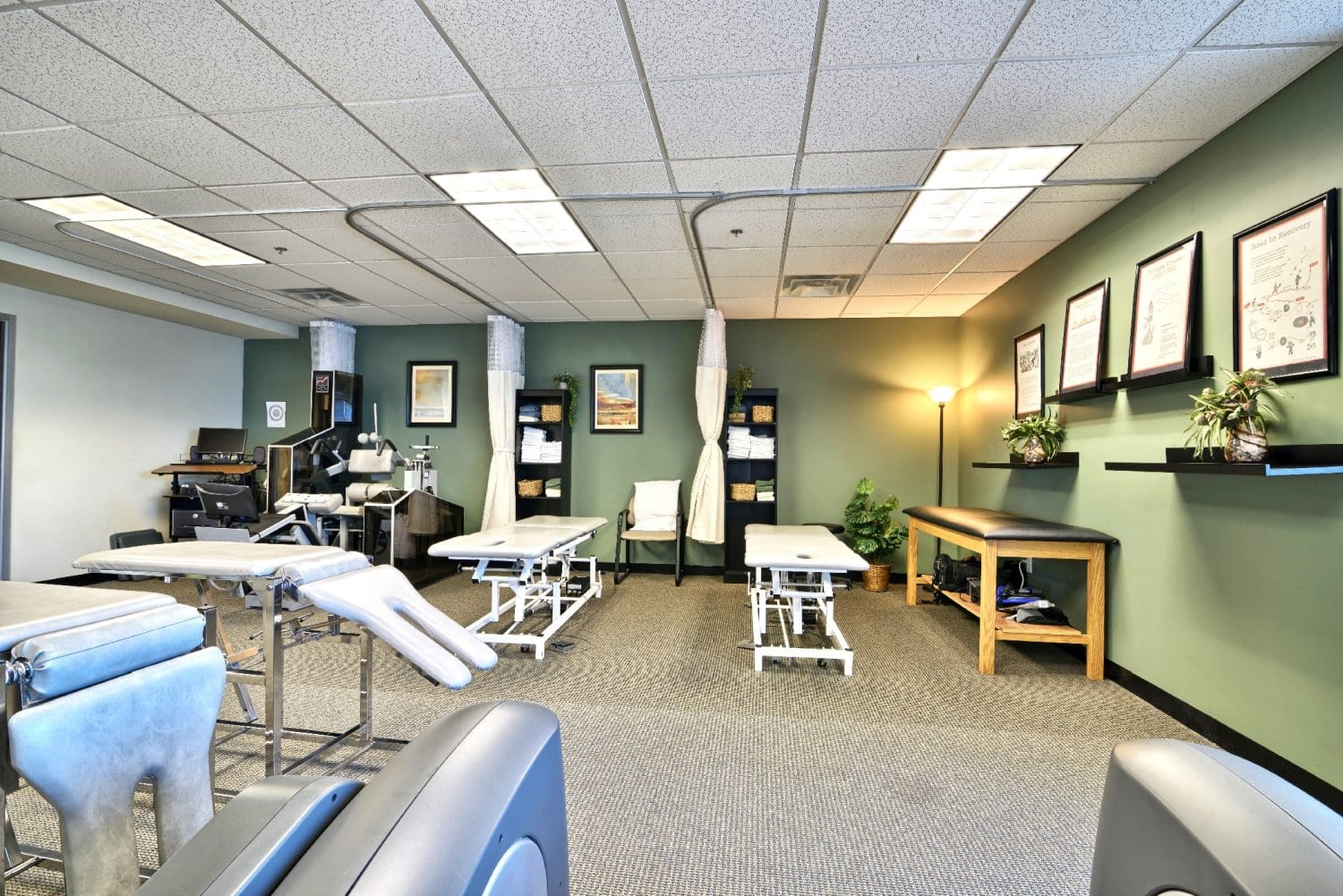 A photo of the interior of our physical therapy clinic. The walls are light green and there are stretch beds in the photo. The facility is in Woburn, Massachusetts.