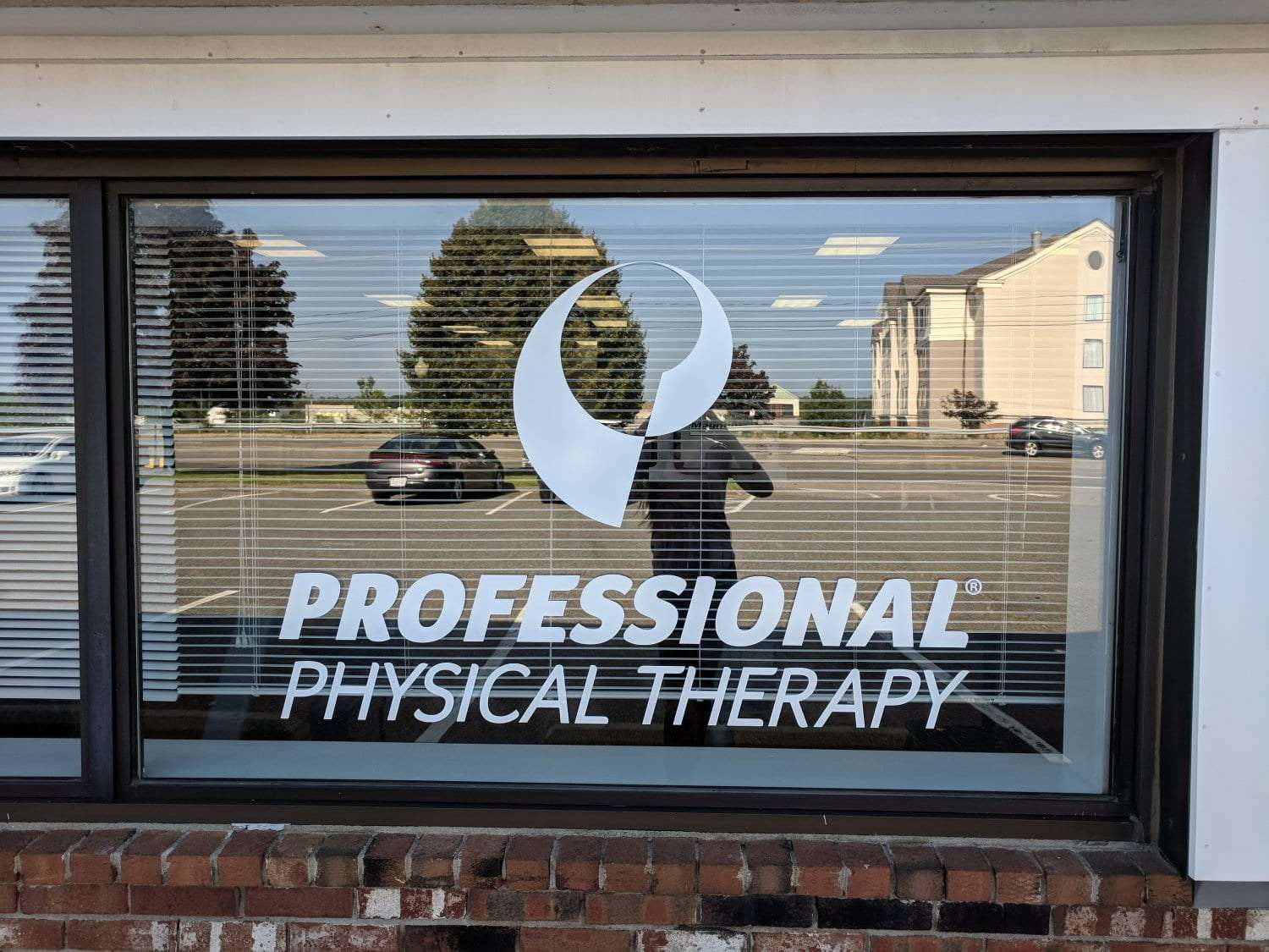 This is an image of the Professional Physical Therapy sign on the window at our clinic in Plymouth, Massachusetts.