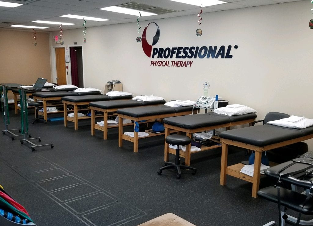 Picture of the main room with logo on wall and therapy beds at our Professional Physical Therapy clinic in Smithtown, NY