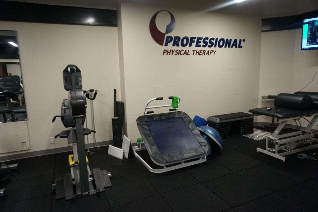 Professional physical therapy clinic in Manhattan NYC Upper West Side with view of excersize room and logo on wall.