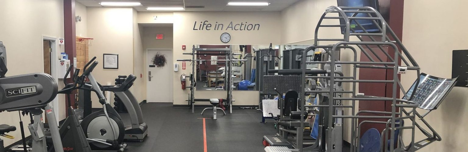 Wide view interior shot of our physical therapy clinic in Norwalk, CT with the Life in Action logo on the wall and exercise equipment.