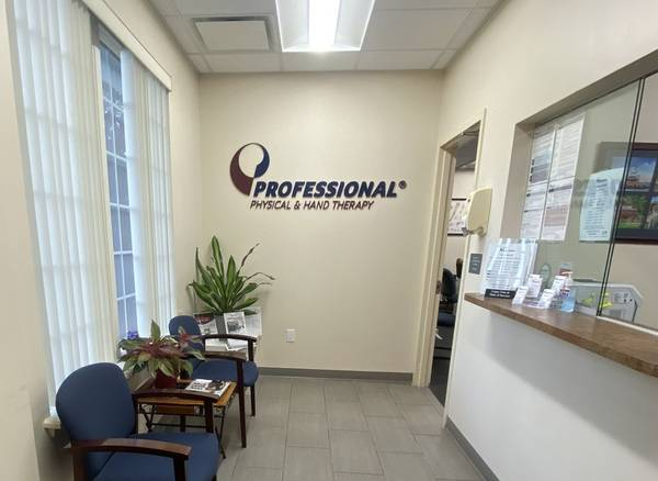 Waiting room and entrance of our Riverhead, NY physical therapy and hand therapy clinic with logo on the wall.