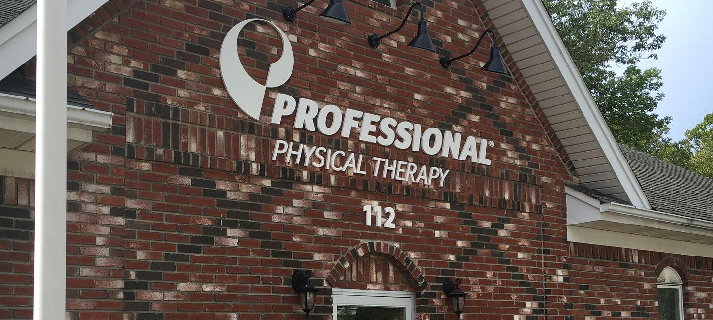 Entrance of our physical therapy and hand therapy clinic in Caldwell NJ with white logo on brick building..