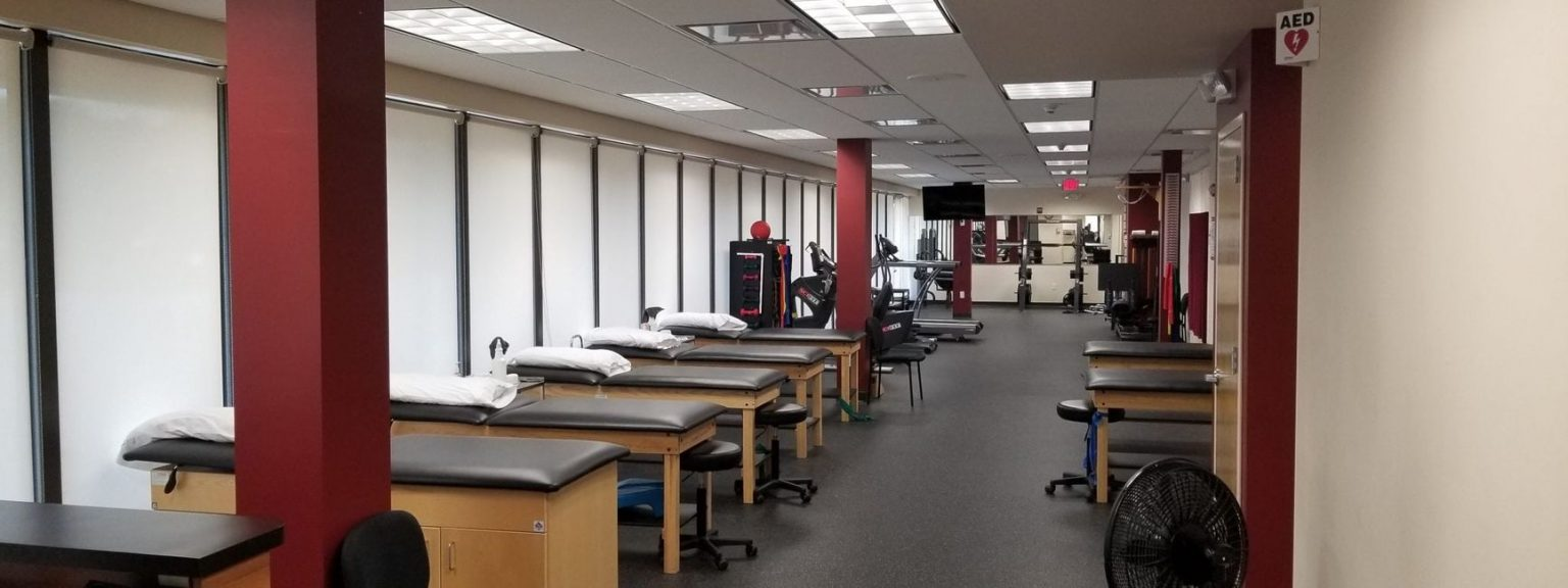 Interior with treatment tables and red posts in our physical therapy clinic in East Englewood, NJ.