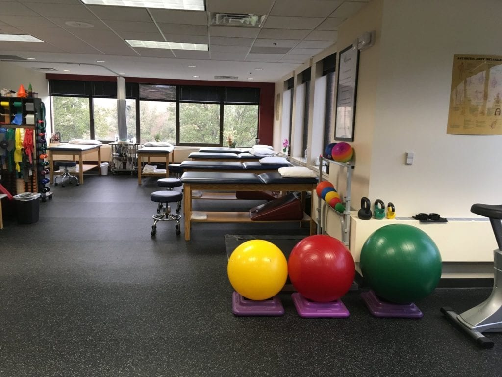 A photo of the training room at our physical therapy clinic in Oradell, New Jersey. The image shows three exercise balls and six stretch beds.