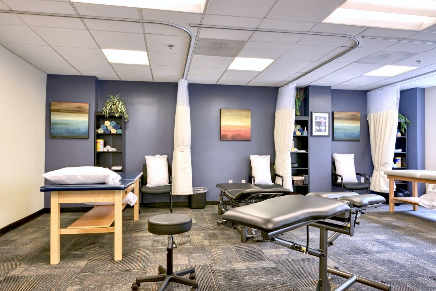 A photo of the interior of our physical therapy clinic in Boston, Massachusetts. This images shows four stretch beds and a purple wall.