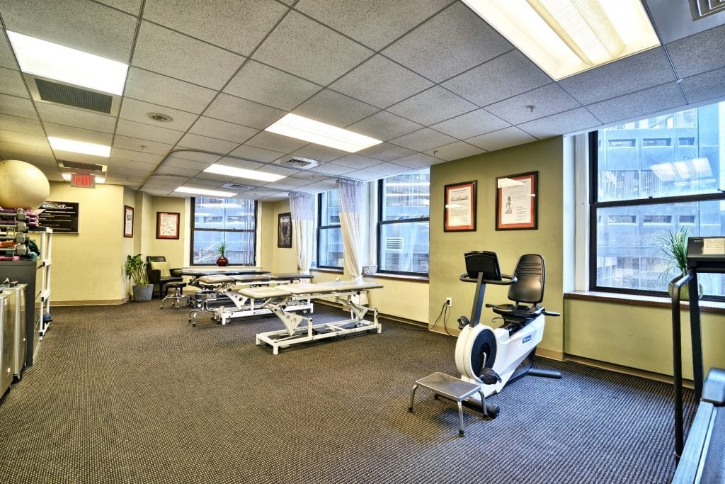 Here is an image of stretch beds and a bike at our physical therapy clinic in Boston, Massachusetts.