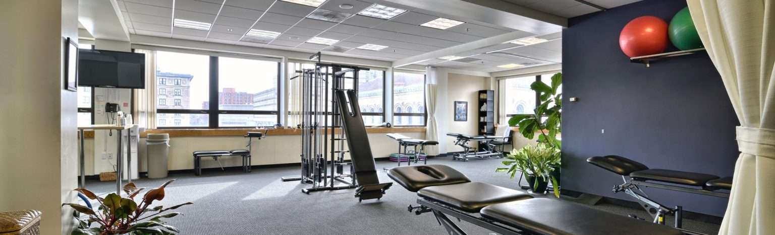 An image of the interior of our physical therapy clinic in Back Bay Boston, Massachusetts with windows facing the skyline.