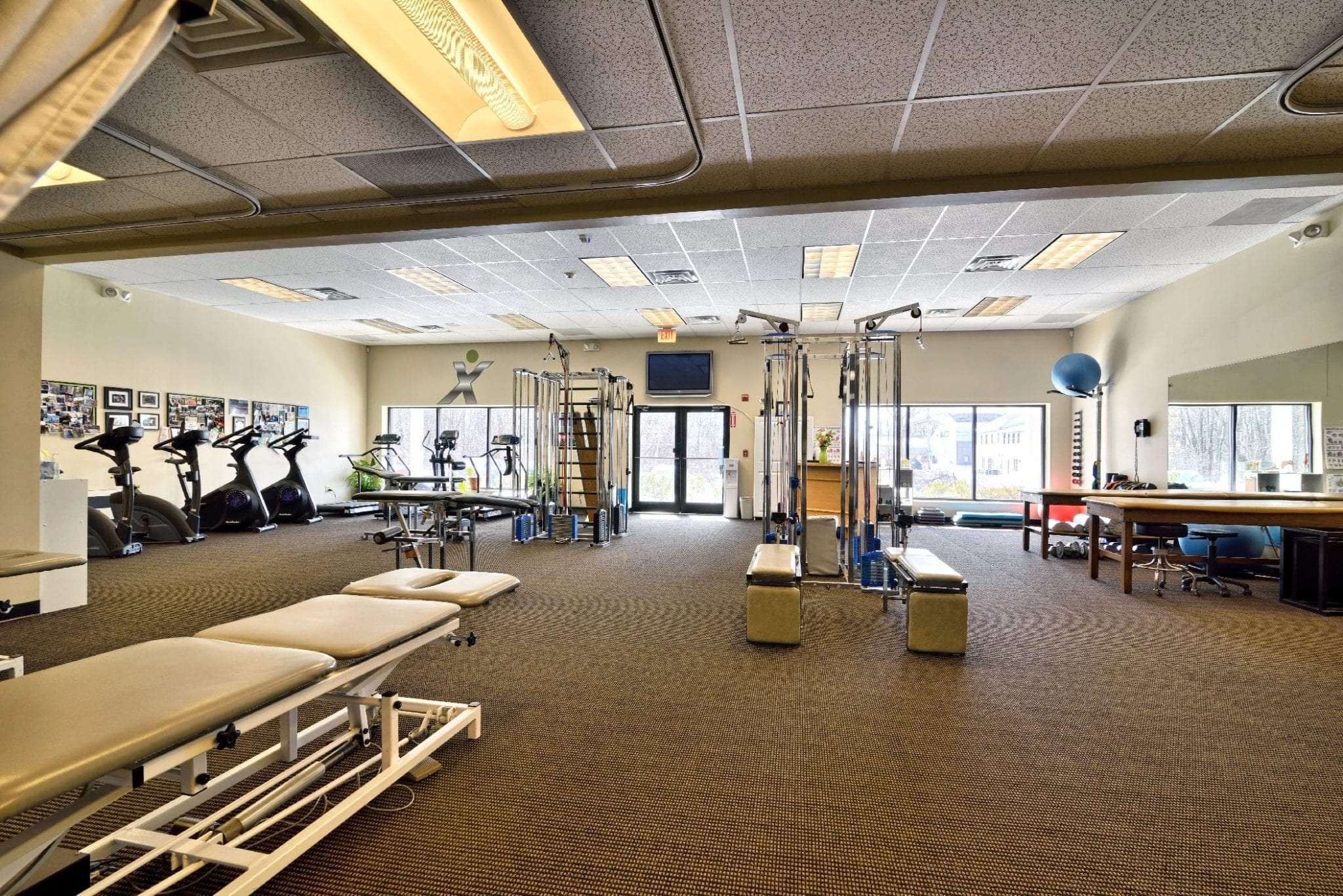 Here is an image of bikes, stretch beds, and weights at our physical therapy clinic in Stratham, New Hampshire.