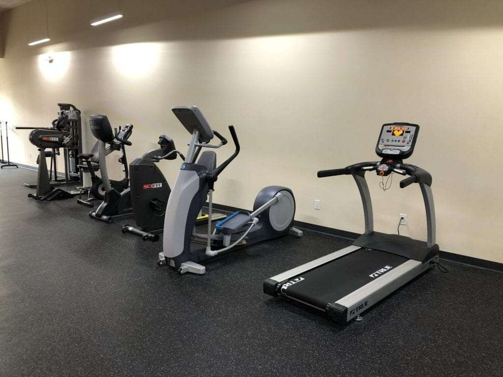 This is an image of some of the equipment used at our physical therapy clinic in Bay Shore, New York. There is a treadmill and elliptical in the photo.