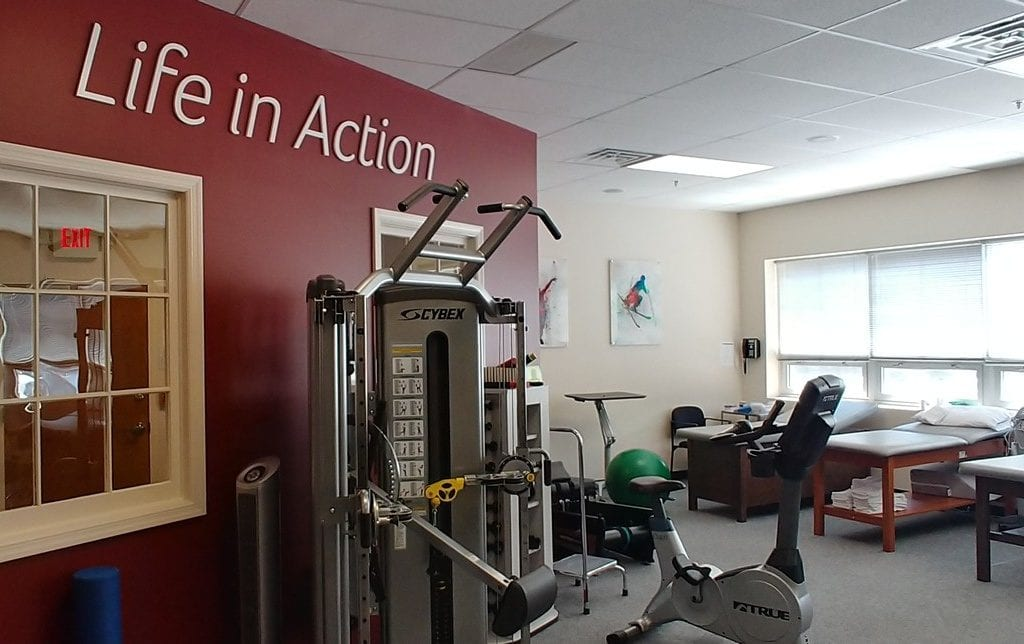 Professional physical therapy clinic in Mount Kisco, NY interior therapy room with red wall.