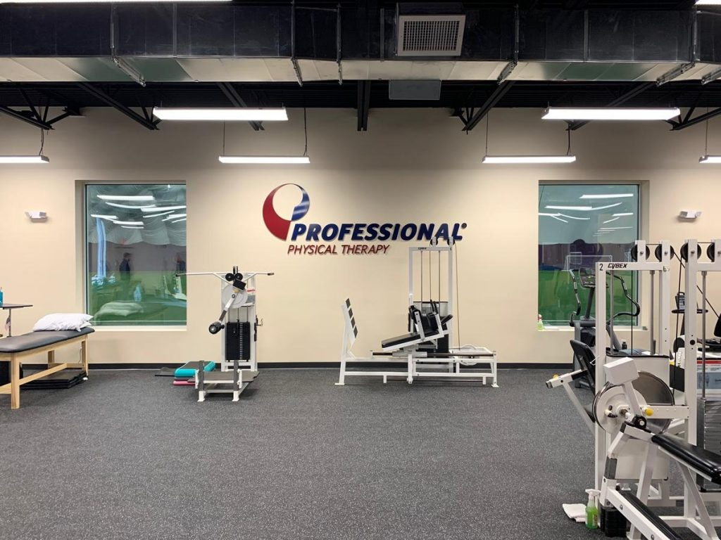 Interior of our physical therapy and sports medicine clinic in Florham Park NJ with equipment and a turf athletic training field in the windows.
