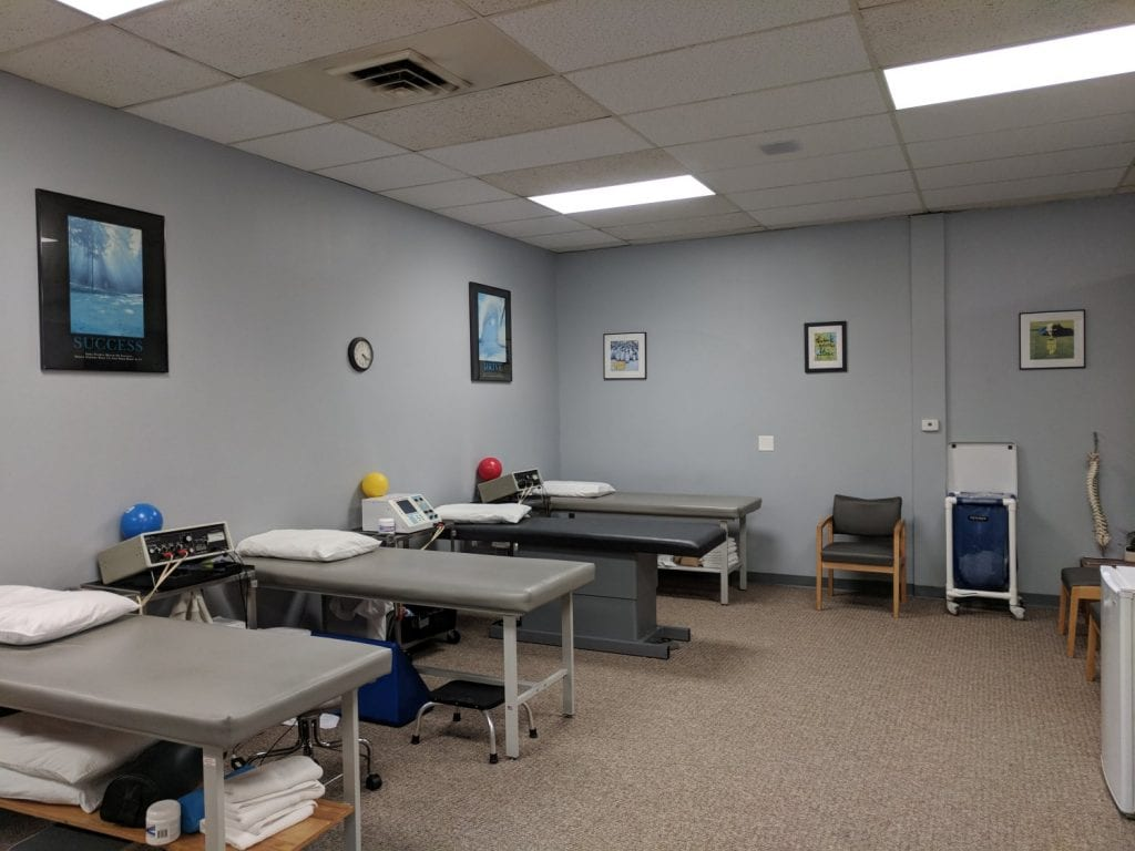 This is an image of the interior of our physical therapy clinic in Plymouth, Massachusetts. Here are four stretch beds. The walls are gray.
