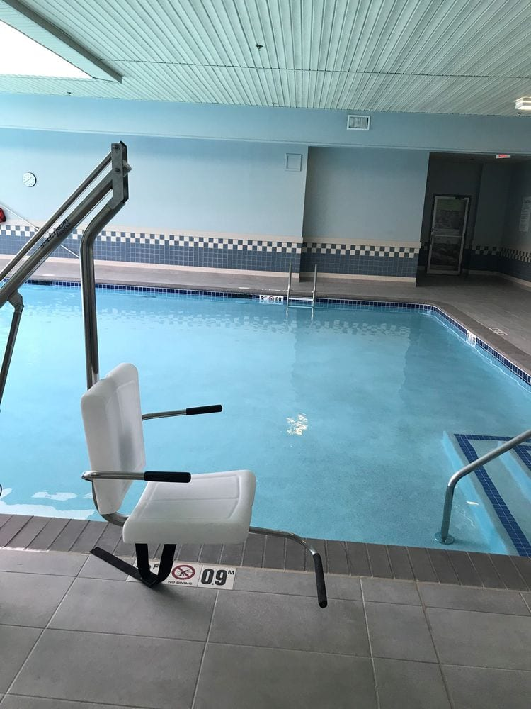 Professional physical therapy clinic in Taunton, MA indoor pool and white chair.