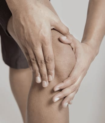 Hands on a knee experiencing pain.