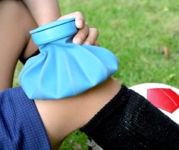 Blue ice pack on a knee of a soccer player.