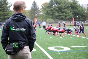 Professional athletic training specialist on the field at a school football game.