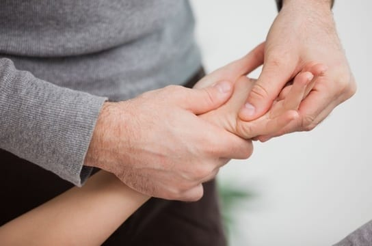 A Professional physical therapist working on the left hand of a patient.