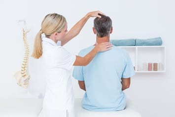 Professional physical therapist looking at a patient's spine and neck.