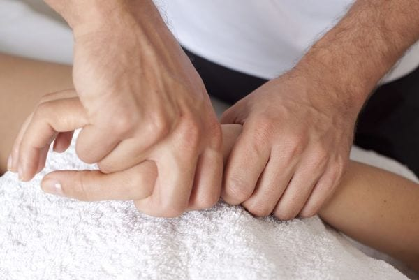 Occupational hand therapist working on patient for hand pain treatment.