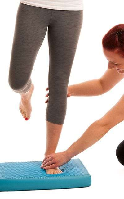 Female physical therapist with a patient in Manhattan NYC doing balance training on a blue mat.