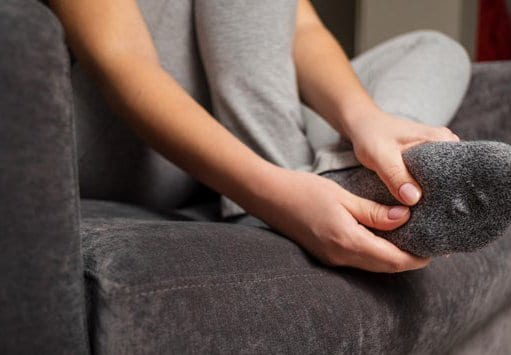 Woman with ball of foot pain sitting on a couch.