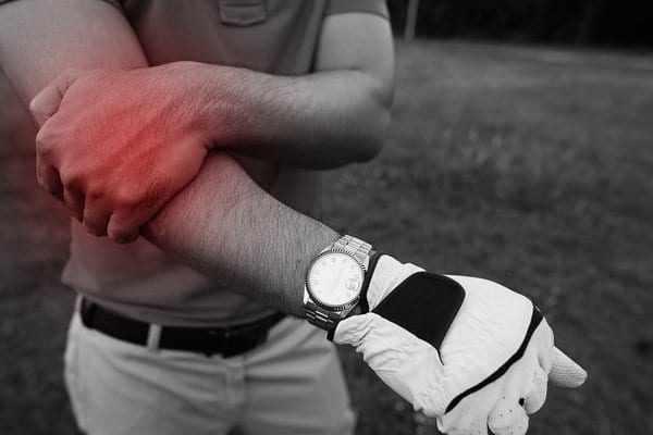 Right arm of a golfer being held with red circle representing elbow pain from golfers elbow.