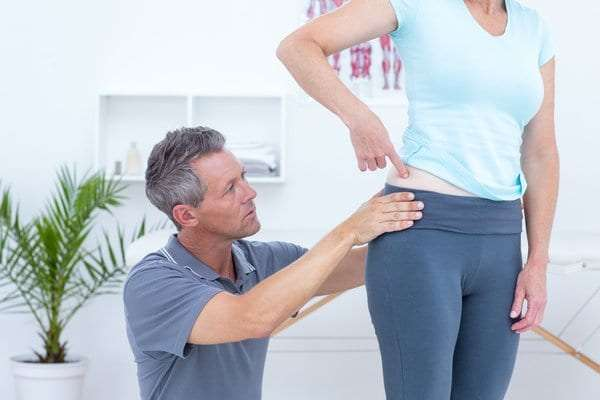 Professional physical therapist assessing a patient for hip pain injuries.
