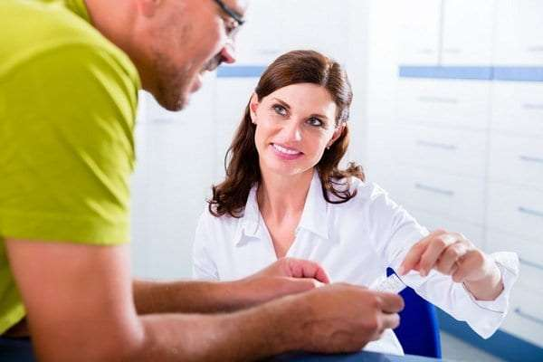 Physical therapists helping a patient with their health insurance card after a physical therapy appointment.