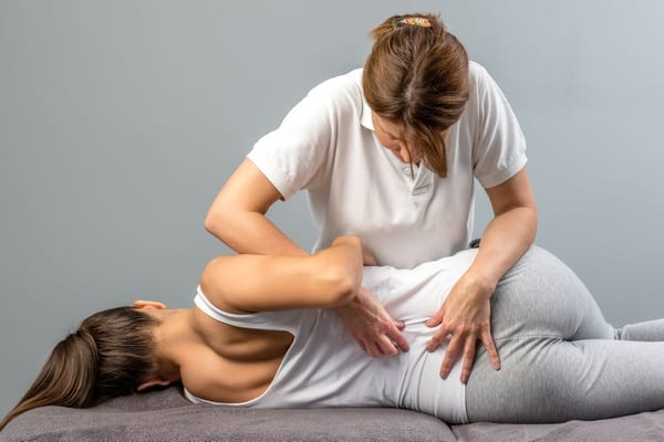 Professional physical therapist performing womens physical therapy on the lower back and spine.