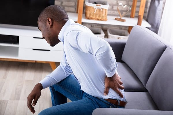 Man on couch holding his lower back in pain
