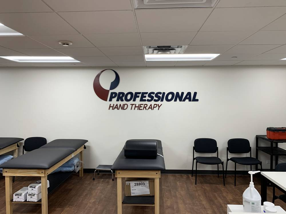 Therapy beds and chairs with the Professional Hand Therapy logo on the wall at our Scarsdale, NY clinic.