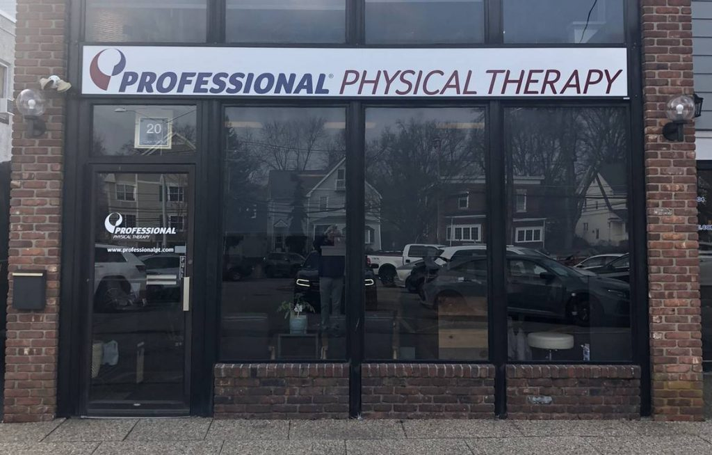 Exterior of our physical therapy clinic in Madison, NJ with sign over glass doors and a brick building.